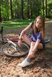 坐在她的自行车附近的妇女在公园,做她的鞋带,袜子 免版税库存照片