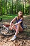 坐在她的自行车附近的妇女在公园 库存照片
