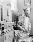 坐在她的虚荣前面的妇女把香水放在她的眼眉上(所有的人被描述不是更长生存和前没有的庄园 免版税库存照片