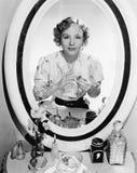 坐在她的虚荣前面的妇女调查镜子(所有人被描述不更长生存,并且庄园不存在 Su 免版税库存图片