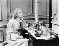 坐在她的虚荣的妇女调查镜子(所有人被描述不更长生存,并且庄园不存在 供应商wa 免版税库存图片