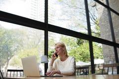 坐在她的设计师时髦的光和宽广的办公室的年轻美丽的女孩运作在膝上型计算机 免版税库存照片