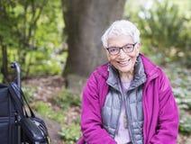 坐在她的轮椅旁边的公园的老妇人 免版税库存照片