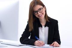 坐在她的worplace的愉快的女实业家 免版税库存图片