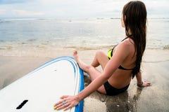坐在委员会旁边的女性冲浪者在冲浪在海滩以后 库存照片
