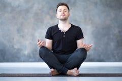 坐在姿势的瑜伽男性初学者实践的瑜伽和思考 免版税图库摄影