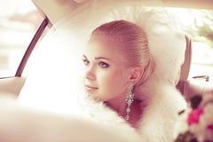 坐在婚礼汽车的美丽的白肤金发的新娘画象  库存照片