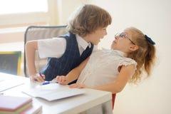 坐在学校书桌的两个年轻人学生、男孩和女孩 免版税库存图片
