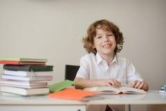 坐在学校书桌的微笑的男孩 免版税图库摄影