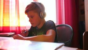 坐在学校书桌的男孩和做工作 学校教育 太阳` s通过玻璃发出光线 股票视频
