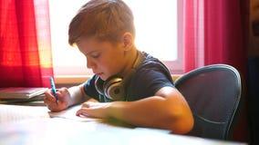 坐在学校书桌的男孩和做工作 学校教育 太阳` s通过玻璃发出光线 影视素材