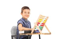 坐在学校书桌的逗人喜爱的矮小的男小学生 库存照片