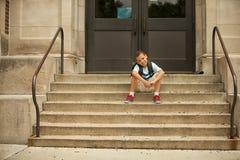 坐在学校外面 免版税库存照片