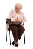 坐在学校椅子和写的年长妇女 免版税图库摄影