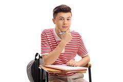 坐在学校椅子的少年学生 库存照片