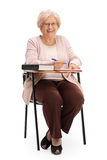 坐在学校椅子的快乐的成熟妇女 库存图片