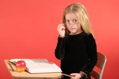 坐在学校的小女孩 免版税库存图片