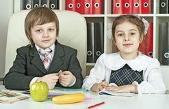 坐在学童的一张桌上的男孩和女孩 免版税库存照片