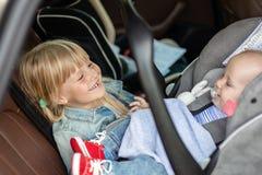 坐在安全位子的汽车的兄弟和姐妹 乘客位置的兄弟姐妹获得乐趣一起在旅行期间  库存照片