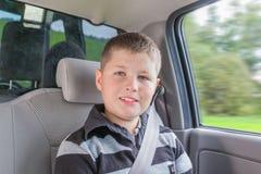 坐在安全椅子的一辆汽车的少年 免版税图库摄影