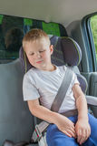 坐在安全椅子的一辆汽车的男孩紧固  免版税库存图片