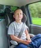 坐在安全椅子的一辆汽车的男孩 免版税库存照片