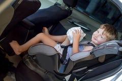坐在安全椅子的一辆汽车的男孩 库存图片