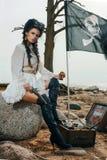 坐在宝物箱附近的海盗妇女 免版税库存照片