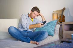 坐在客厅沙发长沙发网络的凉快的可爱和愉快的人放松了享受互联网社会媒介app使用实习生 免版税图库摄影