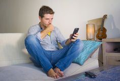 坐在客厅沙发长沙发网络的凉快的可爱和愉快的人放松了享受互联网社会媒介app使用实习生 免版税库存图片