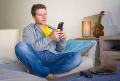 坐在客厅沙发长沙发网络的凉快的可爱和愉快的人放松了享受互联网社会媒介app使用实习生 免版税库存照片