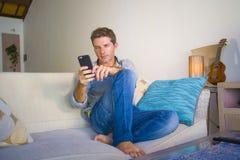 坐在客厅沙发长沙发网络的凉快的可爱和愉快的人放松了享受互联网社会媒介app使用实习生 图库摄影