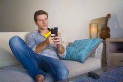 坐在客厅沙发长沙发网络的凉快的可爱和愉快的人放松了享受互联网社会媒介app使用实习生 库存图片