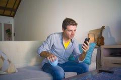 坐在客厅沙发长沙发网络的凉快的可爱和愉快的人放松了享受互联网社会媒介app使用实习生 库存照片