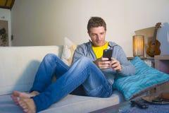 坐在客厅沙发长沙发网络的年轻凉快的可爱和愉快的人放松了享受互联网社会媒介app使用 免版税库存照片