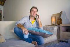 坐在客厅沙发长沙发网络的年轻凉快的可爱和愉快的人放松了谈话有在流动pho的交谈 免版税库存图片