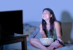 坐在客厅沙发长沙发观看的电视喜剧夜间吃popc的年轻俏丽和愉快的亚裔韩国妇女 库存图片