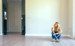 坐在客厅的体贴的女孩 免版税库存图片