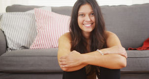 坐在客厅的妇女笑和微笑 库存图片