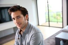 坐在客厅的英俊的年轻人 免版税库存图片