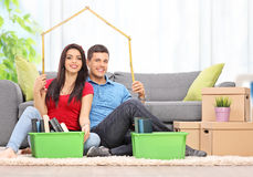 坐在客厅的年轻夫妇 免版税库存照片