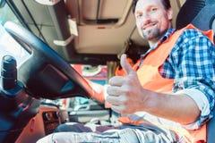 坐在客舱的卡车司机给翘拇指 免版税图库摄影