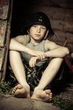 坐在客舱的盔甲的镇静小男孩 图库摄影