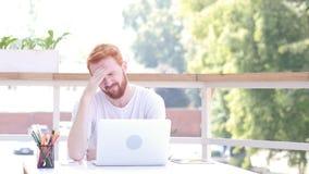 坐在室外办公室,红色头发的紧张,被注重的,被挫败的人 库存照片