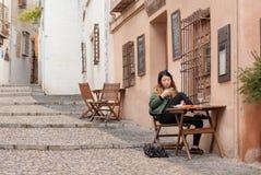 坐在室外咖啡馆和观看在有信使的电话的女孩 库存照片