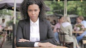 坐在室外咖啡馆的严肃的非洲女实业家 影视素材
