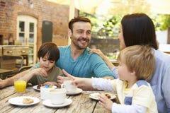 坐在室外咖啡馆表上的家庭吃午餐 免版税库存照片