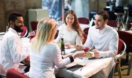 坐在室外餐馆的两对愉快的夫妇 免版税库存图片
