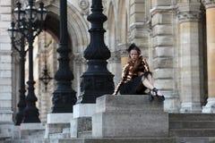 坐在宫殿前面的黑裙子的美丽的芭蕾舞女演员 免版税库存图片