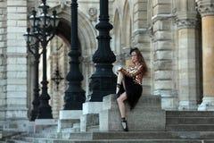 坐在宫殿前面的黑裙子的美丽的芭蕾舞女演员 图库摄影